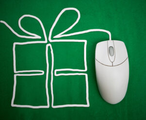 a wired mouse sits on a green surface; its wire is arranged to look like a present