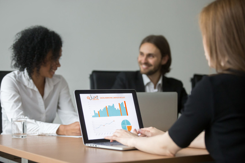 Three young business persons sit at a meeting table with laptops displaying graphs and talking
