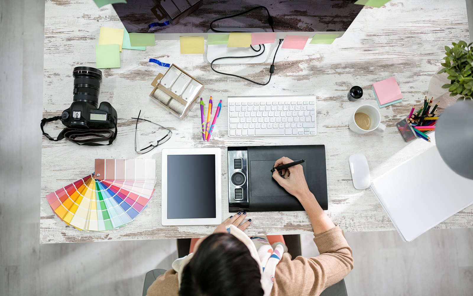 Top-down view of a woman sitting at a desk, writing on a digital drawing pad; the desk is covered in various office supplies (camera, paint swatches, mouse/keyboard, digital drawing pad)
