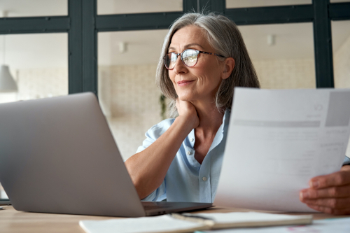 Smiling Mature Middle Aged Business Woman Working on Laptop