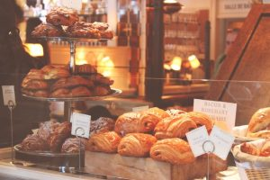 Display window of a bakery stuffed with a large amount of pastries, glazed and almond croissants, and bacon and rosemary fougasse.