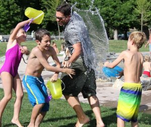 Group of smiling boys and girls dressed in bathing suits pouring water onto a counselor outside on a sunny day.
