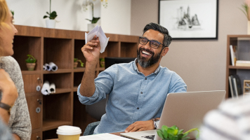 Cheerful mature business man playing with paper plane in office. Team of designers having fun while middle eastern man throwing plane on happy colleagues. Portrait of smiling businessman enjoying.